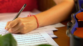 Girl composes music in music sheet book . stock video