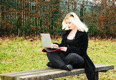 Girl on computer. View of a young woman outdoors on a laptop computer Royalty Free Stock Photo