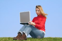 Girl and a computer. Attractive girl with a computer, sitting on a green grass on a background of the blue sky Royalty Free Stock Image