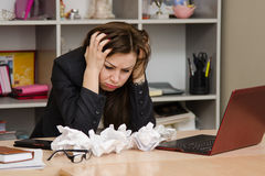 The girl at a computer with bunch crumpled sheets of paper Stock Image