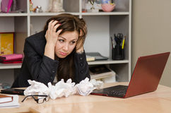 The girl at computer with a bunch of crumpled sheets paper Stock Photos