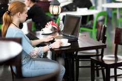 Girl with computer in cafe royalty free stock image