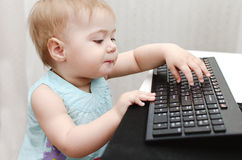 Girl with computer, she's trying to type. NGirl sitting at a computer desk royalty free stock image