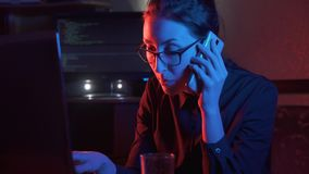 Girl at the computer talking on the phone. Girl in glasses at the computer talking on the phone concept idea stock video footage