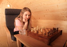 Girl concentrated for next move in chess. Blond Caucasian kid - young hairy girl sitting on armchair and concentrating for next move in chess in wooden attic Stock Image