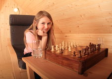 Girl concentrated for next move in chess. Blond Caucasian kid - young hairy girl sitting on armchair and concentrating for next move in chess in wooden attic Royalty Free Stock Images