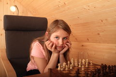 Girl concentrated for next move in chess. Blond Caucasian kid - young hairy girl sitting on armchair and concentrating for next move in chess in wooden attic Stock Photo