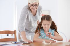 Girl concentrated on quill. Young girl concentrated on quill on a desk tabletop Stock Image