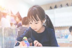 Girl is concentrating on her art work in classroom. Little girl is concentrating on her art work in classroom stock photo