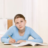 Girl concentrating on homework assignment stock images