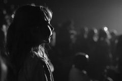 Girl at concert. Girl at a concert in silhouette with light on her face Stock Image