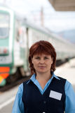 Girl-conductor smiles. Girl-female attendant in uniform. Railway Royalty Free Stock Photo
