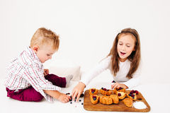 Girl confectioner shouting at brother disturbing. Girl confectioner shouting at her brother disturbing her cooking. Children preparing sweet cakes, little boy Stock Image