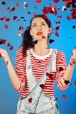 Girl with confetti. Happy girl on blue background, red hearts confetti slowly scatter and fall Stock Photo