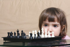 Girl considering chess position Stock Photography