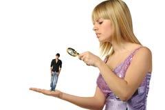 The girl considering the guy through a magnifier Stock Photos