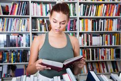 Girl considers the book in a bookstore stock image