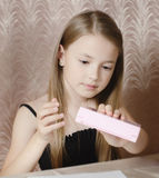 The girl considers a box with children's cosmetics Royalty Free Stock Image