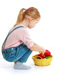 Girl considers lying in a basket of fruit. Royalty Free Stock Photos