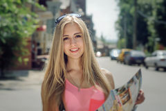 Girl considers the tourist map and smiling Stock Image