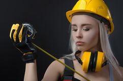 Girl in a construction firm works with a tape measure. The girl in a construction firm works with a tape measure royalty free stock images