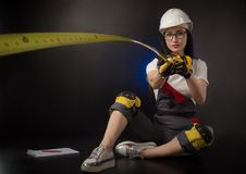 Girl in a construction firm works with a tape measure. The girl in a construction firm works with a tape measure stock photography