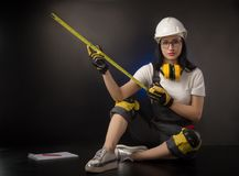 Girl in a construction firm works with a tape measure. The girl in a construction firm works with a tape measure stock photos