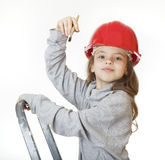 Girl in the construction helmet with a brush. Stock Photography