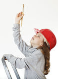 Girl in the construction helmet with a brush. Stock Photos