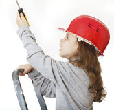 Girl in the construction helmet with a screwdriver. Stock Photo