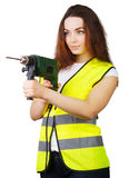 The girl in a construction vest with an electric drill in hands. Royalty Free Stock Image