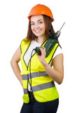The girl in a construction vest and a helmet with an electric drill. Stock Photo