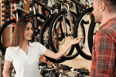 A girl consultant shows the buyer in a bicycle store. Stock Photos