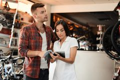 A girl consultant shows the buyer in a bicycle store. Stock Image