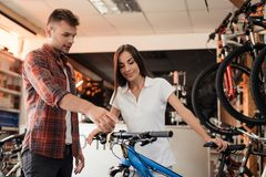 A girl consultant shows the buyer in a bicycle store. A young men came to the store to buy a new bicycle. She helps him to choose stock image
