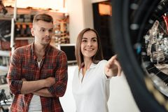 A girl consultant shows the buyer in a bicycle store. Stock Photo