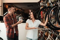 A girl consultant shows the buyer in a bicycle store. Royalty Free Stock Photos