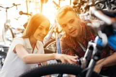 A girl consultant shows the buyer in a bicycle store. Royalty Free Stock Photography