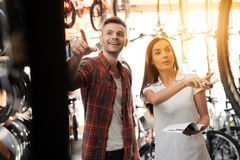A girl consultant shows the buyer in a bicycle store. Royalty Free Stock Images