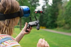 The girl controls a quadrocopter in the park with the help of a VR helmet. The concept of virtual reality. extra reality. / royalty free stock image