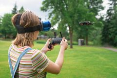 The girl controls a quadrocopter in the park with the help of a VR helmet. The concept of virtual reality. extra reality. / royalty free stock photos