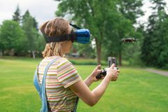 The girl controls a quadrocopter in the park with the help of a VR helmet. The concept of virtual reality. extra reality. / stock photos