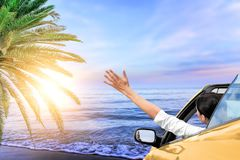 A girl in a convertible car by the sea stretches her hand to the sun at sunset. Vacation. stock photos