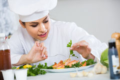 Girl in cook cap with dish of shrimps Royalty Free Stock Image