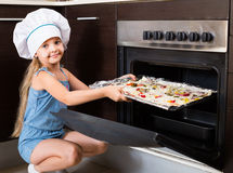 Girl in cook cap near oven with pizza Royalty Free Stock Image
