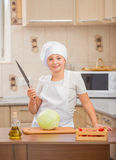 Girl cook cuts cabbage Stock Photography