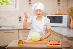 Girl cook cuts cabbage Stock Photos
