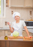 Girl cook cuts cabbage Royalty Free Stock Images