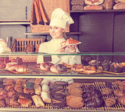 Girl cook gladly suggesting pastry Royalty Free Stock Photo