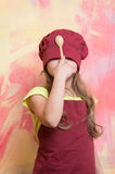 Girl cook hiding face with chef hat and wooden spoon Royalty Free Stock Photo